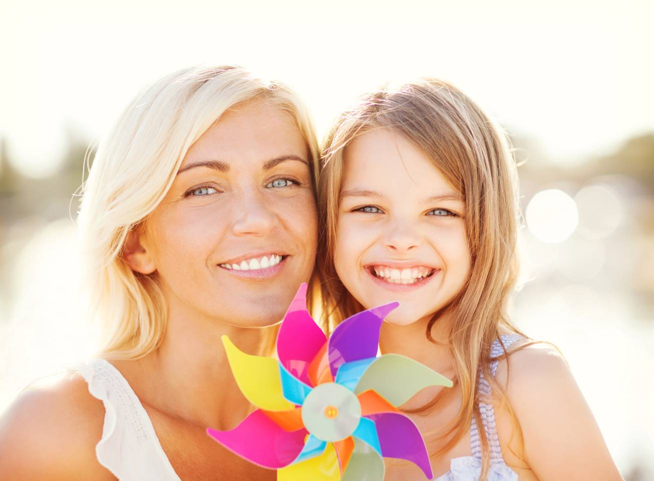 Beautiful mother and daughter smiling outside with white teeth and blue eyes