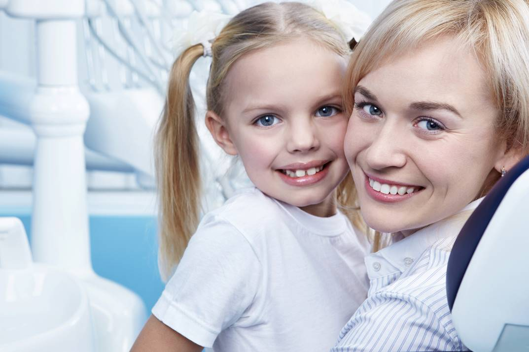 mom and daughter smiling with beautiful teeth