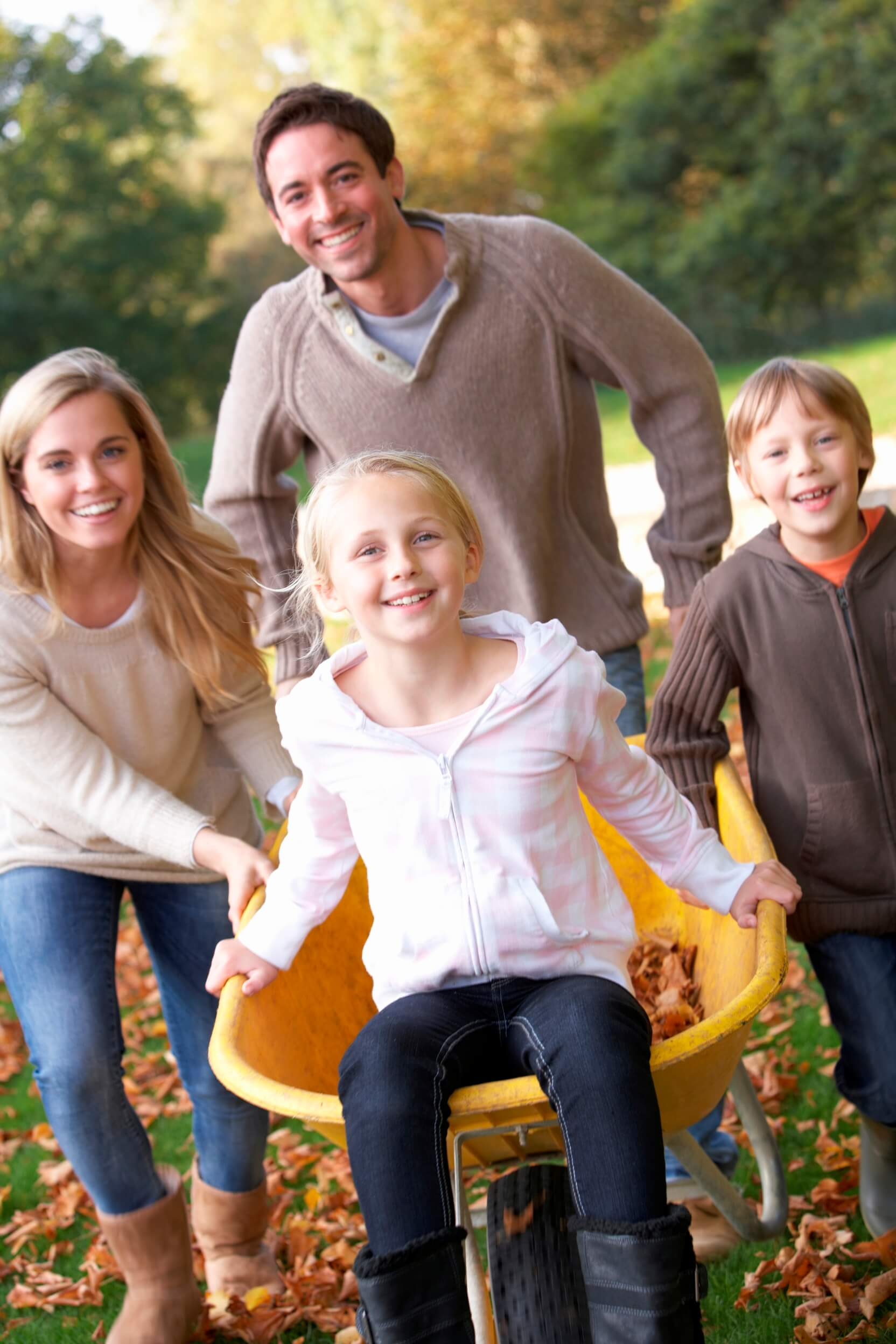 family outside smiling with wheel barrel