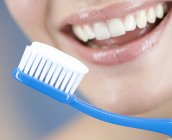 Toothbrush with toothpaste ready to brush with smiling woman in background